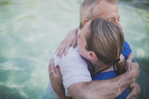 pastor hugging a woman after her baptism in water