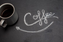 word coffee and arrow pointing to a coffee mug in chalk