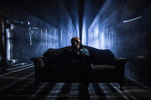 man sitting on a couch in a dark room