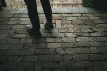 feet in sneakers on cobblestone pavers