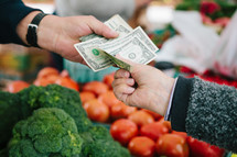 paying for vegetables at a farmers market