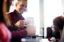A man smiling and drinking coffee at a Christmas party