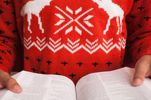 woman in a Christmas sweater reading a Bible