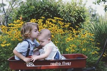 brother and sister in a red wagon near yellow flowers