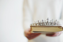 A woman holding a Bible and tiara