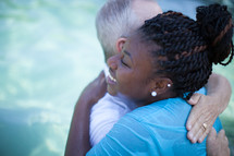 Man and woman hugging after a baptism in a pool of water.