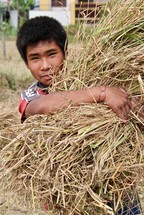 a young man carrying a bundle of hay