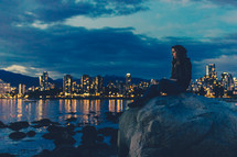 woman sitting on a rock and a view of a coastal city skyline at night