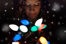 woman holding a strand of glowing Christmas lights