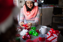A young woman in a santa hat wrapping Christmas presents