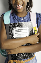 a girl child holding a composition notebook
