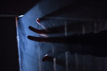 light shining into darkness through cracks and a man's reaching hand