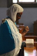 An elderly Ethiopian Orthodox woman in prayer