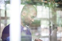 man praying through a window
