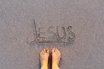 Jesus written in the sands of a beach and bare feet