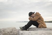 a man praying on a rock beside a quiet lake
