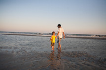 brothers walking holding hands on a beach
