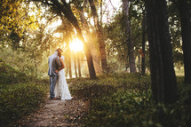bride and groom hugging on a path in a forest