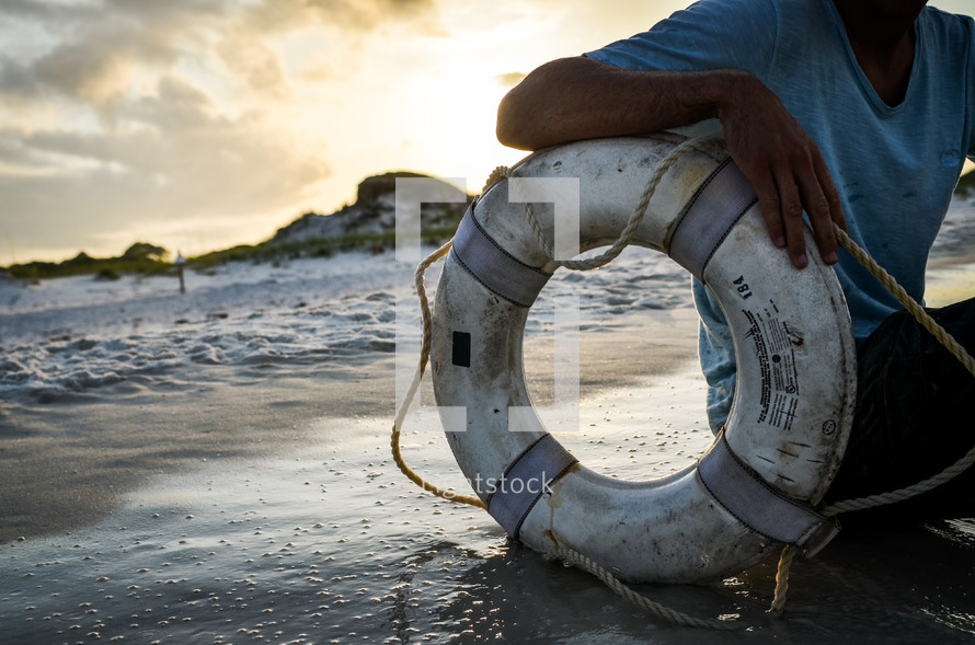 man and a life ring on a beach