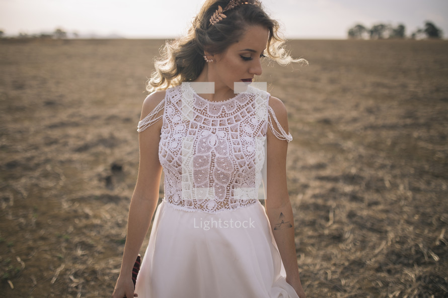 a fall bride standing in a horse pasture