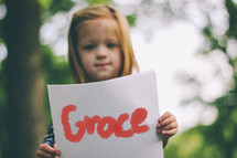 """Child holding a handwritten sign saying, """"Grace."""""""
