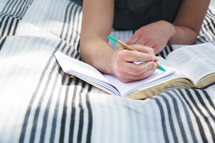 a girl reading a Bible and writing in a journal