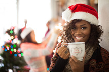 A woman wearing a santa hat and holding a cup of coffee