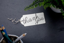 words thank you on a gift tag on a desk