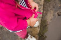 a toddler girl zipping a jacket