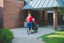 husband pushing his wife in a wheelchair in front of a nursing home
