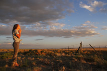 teen girl praying in a field at sunset