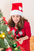 woman decorating a Christmas tree