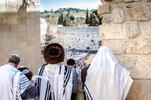 Orthodox Jews looking down at people praying at the Wailing Wall during a Jewish holiday.