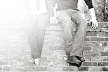 couple holding hands sitting on a brick wall