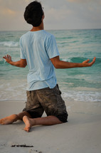 man kneeling in prayer on a beach