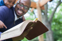 A smiling father and young son reading the Bible.