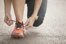 Hands tying a running shoe.