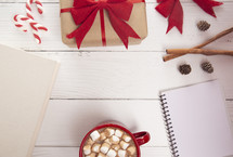 A Holiday Background with Hot Chocolate with Marshmallows and a Nice Book to Read and a Gift
