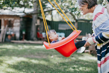 a grandmother pushing a toddler girl on a swing