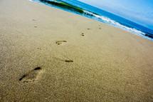 Footprints in the sand near the ocean.