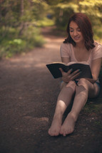woman sitting outdoors reading a Bible