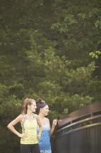 Women walking across a bridge in a park.