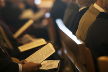 parishioners sitting in church pews with open hymnals and worship books