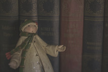 A winter man figurine in front of books on a shelf