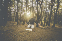 a man kneeling in prayer in a forest near an open Bible