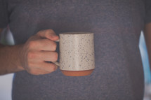 A hand holding a white coffee mug