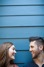A man and woman smiling at each other against a blue wall.