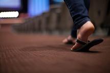feet of a woman walking down the aisle of a church