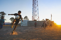children playing soccer in the dirt