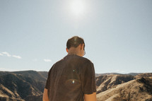a man standing at the top of a mountain looking down